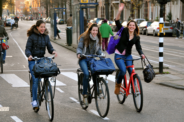 three people happy cycling